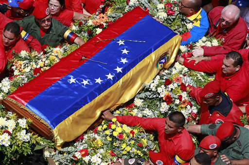 The flag-draped coffin containing the body of Venezuela&#39;s late President Hugo Chavez is taken from the hospital where he died, to a military academy, where it will remain until his funeral in Caracas, Venezuela, Wednesday, March 6, 2013. Seven days of mourning were declared, all schools were suspended for the week and friendly heads of state were expected for an elaborate funeral Friday. &#40;AP Photo&#47;Ricardo Mazalan&#41; <span class=meta>(AP Photo&#47; Ricardo Mazalan)</span>