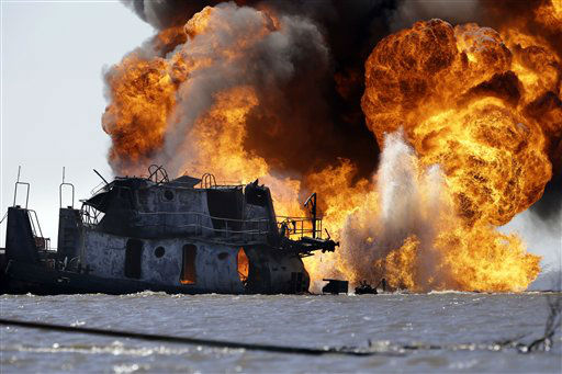 "<div class=""meta ""><span class=""caption-text "">A fire still burns Wednesday, March 13, 2013, after a tugboat and barge hit a gas pipeline Tuesday evening in Perot Bay in Lafourche Parish, La., about 30 miles south of New Orleans. Coast Guard Cmdr. Russ Bowen said it appears the barge is intact and none of its cargo of crude oil was leaking, though there were patches of oily sheen in the area. The Coast Guard was investigating whether those sheens were related to the accident. (AP Photo/Gerald Herbert)</span></div>"