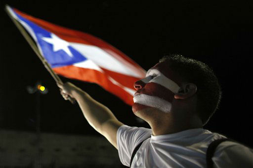 A Puerto Rican fan waves his country&#39;s flag as he watches a live telecast of the World Baseball Classic championship game between Puerto Rico and Dominican Republic in San Juan, Tuesday, March 19, 2013. The Dominican Republic beat Puerto Rico 3-0 on Tuesday night at AT&#38;T Park in San Francisco. &#40;AP Photo&#47;Ricardo Arduengo&#41; <span class=meta>(AP Photo&#47; Ricardo Arduengo)</span>