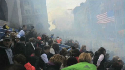 In this image from video provided by Ryan Hoyme, the second explosion can be seen in the distance as smoke from the first explosion surrounds spectators exiting the stands during the Boston Marathon in Boston, Monday, April 15, 2013. (AP Photo/Ryan Hoyme)