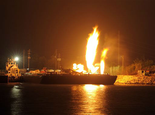 Fire burns aboard two fuel barges along the Mobile River after explosions sent three workers to the hospital Wednesday April 24, 2013. Fire officials have pulled units back from fighting the fire due to the explosions and no immediate threat to lives. &#40;AP Photo John David Mercer&#41; <span class=meta>(AP Photo&#47; John David Mercer)</span>