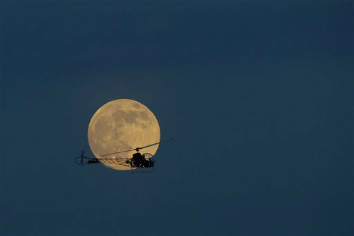 The moon is seen in its waxing gibbous stage as it rises behind the helicopter from the original Batman television show, which people can ride the New Jersey State Fair, Saturday, June 22, 2013, in East Rutherford, N.J. The moon, which will reach its full stage on Sunday, is expected to be 13.5 percent closer to earth during a phenomenon known as supermoon. &#40;AP Photo&#47;Julio Cortez&#41; <span class=meta>(AP Photo&#47; Julio Cortez)</span>