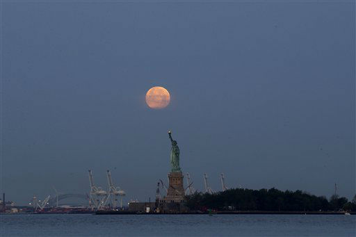 A supermoon glows over the Statue of Liberty, Sunday, June 23, 2013, in New York. The larger than normal moon called the &#34;Supermoon&#34; happens only once this year as the moon on its elliptical orbit is at its closest point to earth and is 13.5 percent larger than usual. &#40;AP Photo&#47;Julio Cortez&#41; <span class=meta>(AP Photo&#47; Julio Cortez)</span>