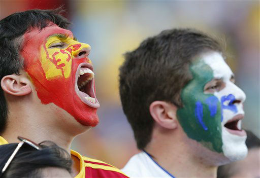 A fan of Spain&#39;s national soccer team, donning the team&#39;s colors, left, shouts, next to a soccer fan who wears the colors representing Italy, prior to the start of the soccer Confederations Cup semifinal match between Spain and Italy at Castelao stadium in Fortaleza, Brazil, Thursday, June 27, 2013. Spain went on to defeat Italy 7-6 on penalties to reach final. &#40;AP Photo&#47;Victor R. Caivano&#41; <span class=meta>(AP Photo&#47; Victor R. Caivano)</span>
