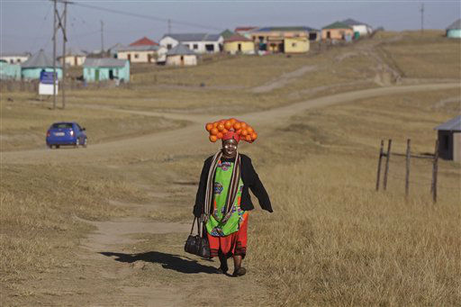 A woman carrying oranges on her head walks to a party in hounor of former South African President Nelson Mandela during celebrations for Mandela&#39;s birthday in Mvezo, South Africa, Wednesday, July 18, 2012. Across the country, and even abroad, people are doing good deeds to honor the country&#39;s most famous statesman on his 94th birthday today. &#40;AP Photo&#47;Schalk van Zuydam&#41; <span class=meta>(AP Photo&#47; Schalk van Zuydam)</span>