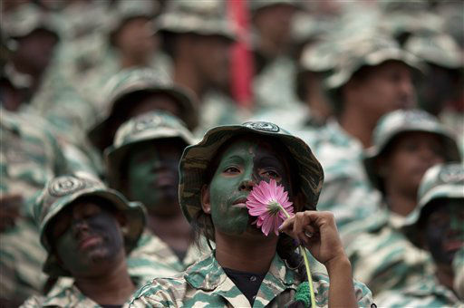 "<div class=""meta ""><span class=""caption-text "">A female member of Venezuela's Bolivarian militia, in uniform with her face painted, holds a flower during a rally in Caracas, Venezuela, Thursday, Jan. 10, 2013. Supporters of Venezuelan President Hugo Chavez rallied outside his presidential palace Thursday in an exuberant symbolic inauguration for a leader too ill to return home for the real thing. With Chavez out of sight in a Cuban hospital fighting a severe respiratory infection more than a month after cancer surgery, his swearing-in ceremony has been indefinitely postponed, despite opposition complaints. (AP Photo/Ariana Cubillos) (AP Photo/ Ariana Cubillos)</span></div>"