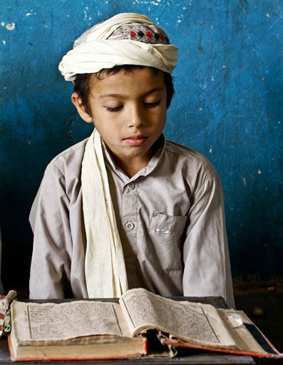 An Afghan boy reads verses of the Holy Quran at a mosque during the Islamic month of Ramadan in Kandahar southern of Kabul, Afghanistan, Thursday, July 11, 2013. &#40;AP Photo&#47;Allauddin Khan&#41; <span class=meta>(AP Photo&#47; Allauddin Khan)</span>