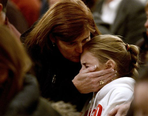 A woman comforts a young girl during a vigil service for victims of the Sandy Hook Elementary shooting, Friday, Dec. 14, 2012, at St. Rose of Lima Roman Catholic Church in Newtown, Conn. &#40;AP Photo&#47;Andrew Gombert, Pool&#41; <span class=meta>(AP Photo&#47; Andrew Gombert)</span>