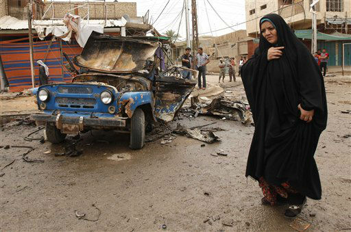 "<div class=""meta image-caption""><div class=""origin-logo origin-image ""><span></span></div><span class=""caption-text"">An Iraqi woman passes by the scene of a car bomb attack in the Kamaliyah neighborhood, a predominantly Shiite area of eastern Baghdad, Iraq, Monday, May 20, 2013. A wave of car bombings across Baghdad's Shiite neighborhoods and in the southern city of Basra killed and wounded scores of people, police said. (AP Photo/ Hadi Mizban) (AP Photo/ Hadi Mizban)</span></div>"