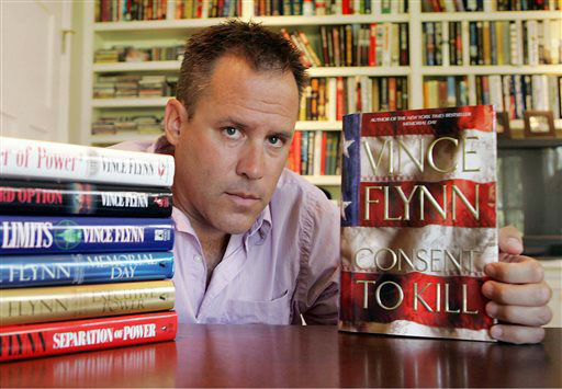 FILE - In a Sept. 2, 2005 file photo, best-selling author Vince Flynn poses with the dust jacket of his new book, &#34;Consent to Kill,&#34; and copies of his six other books in his home in Edina, Minn. Flynn died, Wednesday, June 18, 2013, after a two-year battle with prostate cancer, a statement from Flynn&#39;s publisher, Simon &amp; Schuster, Inc., said. He was 47. &#40;AP Photo&#47;Jim Mone, File&#41; <span class=meta>(AP Photo&#47; JIM MONE)</span>