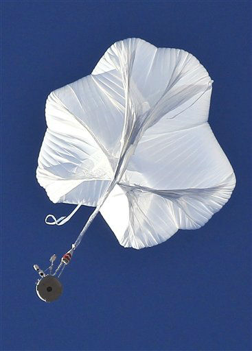 The capsule, bottom left, and attached helium balloon carrying Felix Baumgartner lifts off as he attempts to break the speed of sound with his own body by jumping from a space capsule lifted by a helium balloon, Sunday, Oct. 14, 2012, in Roswell, N.M.  Baumgartner plans to jump from an altitude of 120,000 feet, an altitude chosen to enable him to achieve Mach 1 in free fall, which would deliver scientific data to the aerospace community about human survival from high altitudes.&#40;AP Photo&#47;Ross D. Franklin&#41; <span class=meta>(AP Photo&#47; Ross Franklin)</span>