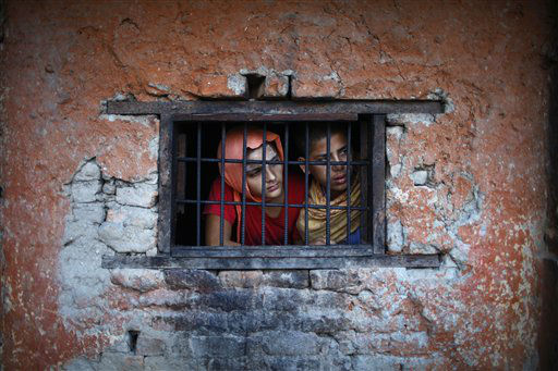 Students from Pashupatinath Veda Vidya Ashram, a school on Hindu religious teaching, look out from a window of their class in Katmandu, Nepal, Thursday, Aug. 16, 2012. &#40;AP Photo&#47;Niranjan Shrestha&#41; <span class=meta>(AP Photo&#47; Niranjan Shrestha)</span>