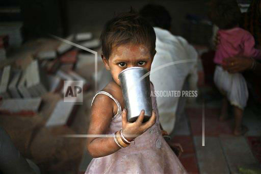 "<div class=""meta ""><span class=""caption-text "">A small girl drinks water from a steel glass as her parents construct a pavement in New Delhi, India, Wednesday, May 8, 2013. The capital is reeling under a heat wave with temperatures touching 40.8 degrees Celsius (105 degrees Fahrenheit) Tuesday, two degrees above normal for this time of the year. (AP Photo/Saurabh Das)  </span></div>"