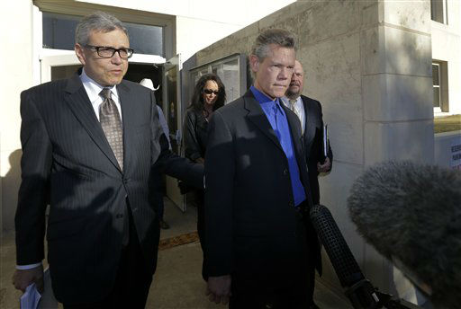 Entertainer Randy Travis, right, exits Grayson County Courthouse with attorney Larry Friedman, left, and other members of his legal team Thursday, Jan. 31, 2013, in Sherman, Texas. Travis plead guilty to driving while intoxicated in a plea agreement with the court and will pay a &#36;2,000 fine and serve a two year probation. &#40;AP Photo&#47;Tony Gutierrez&#41; <span class=meta>(AP Photo&#47; Tony Gutierrez)</span>