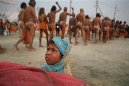 A child  watches as  Hindu holy men of the Juna Akhara sect leave their camp for a rituals that are believed to rid them of all ties in this life and dedicate themselves to serving God as a &#39;Naga&#39; or naked holy men, at Sangam, the confluence of the Ganges and Yamuna River during the Maha Kumbh festival in Allahabad, India, Wednesday, Feb. 6, 2013. The significance of nakedness is that they will not have any worldly ties to material belongings, even something as simple as clothes. This ritual that transforms selected holy men to Naga can only be done at the Kumbh festival. &#40;AP Photo&#47; Rajesh Kumar Singh&#41; <span class=meta>(AP Photo&#47; Rajesh Kumar Singh)</span>