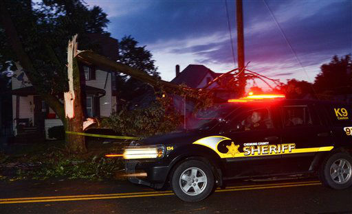 A Chemung County Sheriff rushes past a felled tree after a possible tornado struck the area, Thursday, July 26, 2012, in Elmira N.Y. Power lines and trees were toppled and hospitals were placed on disaster alert but there were no immediate reports of injuries after a possible tornado hit the city of Elmira Thursday afternoon, Chemung County Office of Fire and Emergency Management spokeswoman Karen Miner said.&#40;AP Photo&#47;Heather Ainsworth&#41; <span class=meta>(AP Photo&#47; Heather Ainsworth)</span>