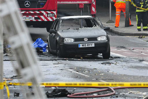 A damaged car remains in the street after a helicopter crashed into a construction crane on top of St George&#39;s Wharf tower building, in London, Wednesday Jan. 16, 2013. Police say two people were killed when a helicopter crashed during rush hour in central London after apparently hitting a construction crane on top of a building. &#40;AP Photo&#47;Vince Pol&#41; <span class=meta>(AP Photo&#47; Vince Pol)</span>