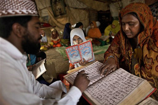Pakistani woman Halimah Tajj, 51, right, repeats after her teacher Mohammad Shiraz, 24, left, during a three hour daily class for illiterate women and children on how to read Urdu alphabet and verses of the holy Quran, in a makeshift tent on the outskirts of Islamabad, Pakistan, Tuesday, April 2, 2013. According to the United Nations, only 40 percent of Pakistani girls 15 or younger are literate in Pakistan. &#40;AP Photo&#47;Muhammed Muheisen&#41; <span class=meta>(AP Photo&#47; Muhammed Muheisen)</span>