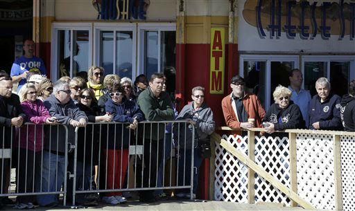 People stand behind a barricade while they wait to catch a glimpse of Britain&#39;s Prince Harry, who is expected to visit Casino Pier during a tour of the area hit by Superstorm Sandy, Tuesday, May 14, 2013, in Seaside Heights, N.J. The prince toured the community&#39;s rebuilt boardwalk, which is about two-thirds complete. New Jersey sustained about &#36;37 billion worth of damage from the storm. &#40;AP Photo&#47;Julio Cortez&#41; <span class=meta>(AP Photo&#47; Julio Cortez)</span>
