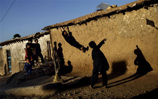 An Afghan refugee boy, right, launches a kite, while other children play nearby, in a poor neighborhood on the outskirts of Islamabad, Pakistan, Tuesday, April 16, 2013. Pakistan hosts over 1.6 million registered Afghans, the largest and most protracted refugee population in the world, according to the U.N. refugee agency. &#40;AP Photo&#47;Muhammed Muheisen&#41; <span class=meta>(AP Photo&#47; Muhammed Muheisen)</span>