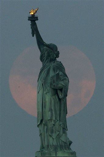 A supermoon sets behind the Statue of Liberty, Sunday, June 23, 2013, in New York. The larger than normal moon called the &#34;Supermoon&#34; happens only once this year as the moon on its elliptical orbit is at its closest point to earth and is 13.5 percent larger than usual. &#40;AP Photo&#47;Julio Cortez&#41; <span class=meta>(AP Photo&#47; Julio Cortez)</span>