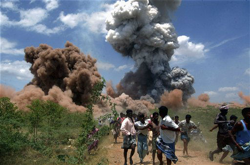 In this Wednesday, Sept. 5, 2012 photo, people run for cover as smoke rises from the site of a fire at a fireworks factory on the outskirts of Sivakasi, about 500 kilometers &#40;310 miles&#41; southwest of Chennai, India.  Police in southern India said they have arrested six employees of the fireworks factory for a massive blaze that killed 40 workers and injured 60 others Wednesday. &#40;AP Photo&#41; INDIA OUT <span class=meta>(AP Photo&#47; Uncredited)</span>