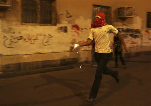 "<div class=""meta ""><span class=""caption-text "">A Bahraini anti-government protester prepares to throw a petrol bomb at riot police during clashes following a rally protesting against the upcoming Formula One race in Sanabis, Bahrain, Tuesday, April 9, 2013. The Bahrain Grand Prix is to be held April 21. Bahrain says four suspects have been arrested after homemade firebombs were hurled at the foreign ministry in a possible escalation of anti-government protests. (AP Photo/Hasan Jamali) (AP Photo/ Hasan Jamali)</span></div>"