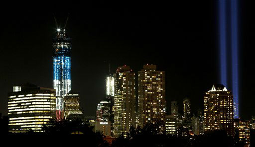 Two light beams, right, known as The Tribute in Light representing the Twin Towers illumincates the sky in Lower Manhattan near the One World Trade Center construction site, left, seen from Jersey City, N.J., in honor of the 11th anniversary of the Sept. 11 terrorist attacks, Tuesday, Sept. 11, 2012, in New York. &#40;AP Photo&#47;Julio Cortez&#41; <span class=meta>(AP Photo&#47; Julio Cortez)</span>
