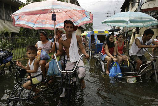 "<div class=""meta ""><span class=""caption-text "">Residents ride a pedicab along a flooded street in Valenzuela city, north of Manila, Philippines on Tuesday July 31, 2012. Typhoon Saola dumped torrents of rain as it swept past the Philippines, killing at least seven people and displacing more than 20,000 others by Tuesday. (AP Photo/Aaron Favila) (AP Photo/ Aaron Favila)</span></div>"