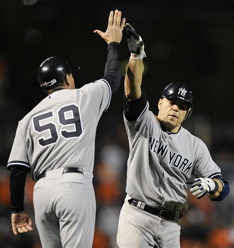 New York Yankees&#39; Russell Martin, right, high-fives third base coach Rob Thomson as he rounds the bases after hitting a solo home run in the ninth inning of Game 1 of the American League division baseball series against the Baltimore Orioles on Sunday, Oct. 7, 2012, in Baltimore. New York won 7-2. &#40;AP Photo&#47;Nick Wass&#41; <span class=meta>(AP Photo&#47; Nick Wass)</span>