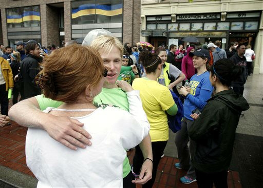 Nick Pelton, of Florida, hugs his mom, Colleen, after watching runners who were unable to finish the Boston Marathon because of the bombings on April 15, cross the finish line on Boylston Street after the city allowed them to finish the last mile of the race, in Boston, Saturday, May 25, 2013. &#40;AP Photo&#47;Winslow Townson&#41; <span class=meta>(AP Photo&#47; Winslow Townson)</span>