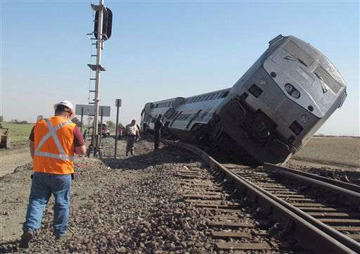 Emergency personnel respond to the scene of a train derailment in Hanford, Calif., Monday, Oct. 1, 2012. Two cars and the locomotive of the train car derailed after colliding with a big rig truck in California&#39;s Central Valley, authorities said. At least 20 passengers suffered minor to moderate injuries, authorities said. The crash occurred when the driver of the big rig carrying cotton trash failed to yield and hit the train, authorities said. The impact pushed the two passenger cars and the locomotive off the tracks south of Hanford, a farming town. &#40;AP Photo&#47;Gosia Woznicacka&#41; <span class=meta>(AP Photo&#47; Gosia Wozniacka)</span>