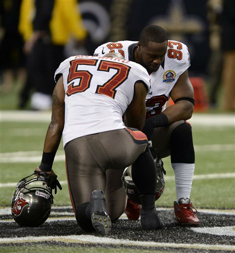 Tampa Bay Buccaneers outside linebacker Adam Hayward &#40;57&#41; and defensive tackle Gerald McCoy &#40;93&#41; pause for a moment of silence in memory of 20 children and six adults killed Friday in a shooting rampage at Sandy Hook Elementary School in Newtown, Conn., before an NFL football game against the New Orleans Saints at the Mercedes-Benz Superdome in New Orleans, Sunday, Dec. 16, 2012. &#40;AP Photo&#47;Bill Feig&#41; <span class=meta>(AP Photo&#47; Bill Feig)</span>