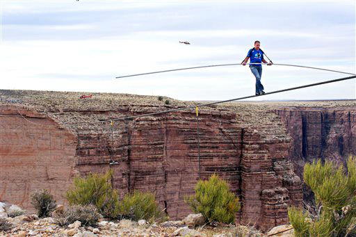 Aerialist Nik Wallenda near the end of his quarter mile walk over the Little Colorado River Gorge in northeastern Arizona on Sunday, June 23, 2013. The daredevil successfully traversed the tightrope strung 1,500 feet above the chasm near the Grand Canyon in just more than 22 minutes, pausing and crouching twice as winds whipped around him and the cable swayed. &#40;AP Photos&#47;Discovery Channel, Tiffany Brown&#41; <span class=meta>(AP Photo&#47; Tiffany Brown)</span>