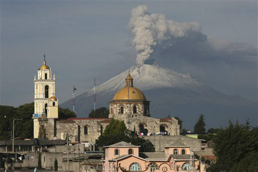 The main church in the town of San Damian Texoloc, Mexico stands in front of the Popocatepetl volcano as is spews ash and vapor early Tuesday, July 9, 2013. Last Saturday, Mexico&#39;s National Center for Disaster Prevention raised the volcano alert from Stage 2 Yellow to Stage 3 Yellow, the final step before a Red alert, when possible evacuations could be ordered after the Popocatepetl volcano spit out a cloud of ash and vapor 2 miles &#40;3 kilometers&#41; high over several days of eruptions. &#40;AP Photo&#47;J. Guadalupe Perez&#41; <span class=meta>(AP Photo&#47; J. Guadalupe Perez)</span>