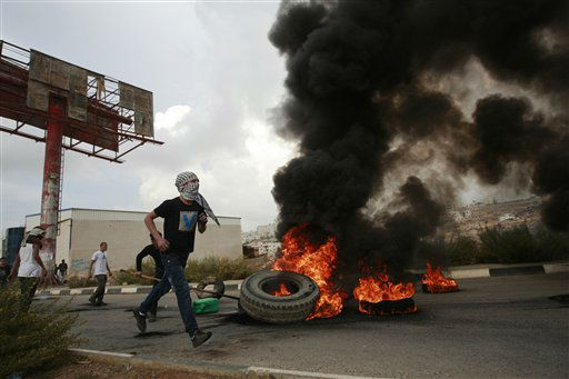 Palestinian burn tyres during a protest against Israel&#39;s operations in Gaza Strip, outside Ofer, an Israeli military prison near the West Bank city of Ramallah, Sunday, Nov. 18, 2012. &#40;AP Photo&#47;Majdi Mohammed&#41; <span class=meta>(AP Photo&#47; Majdi Mohammed)</span>