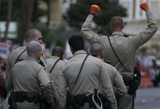 "<div class=""meta ""><span class=""caption-text "">A Las Vegas Metropolitan Police officer holds up his hands as the last protestor is led away during a civil disobedience demonstration by the Culinary Workers Union outside the Cosmopolitan Hotel-Casino, Wednesday, March 20, 2013, in Las Vegas. Nearly 98 protestors were arrested during the demonstration in which they sat on and blocked traffic along Las Vegas Boulevard. Workers have been in contract talks with Cosmopolitan Las Vegas owner Deutsche  Bank for two years. (AP Photo/Julie Jacobson) (AP Photo/ Julie Jacobson)</span></div>"