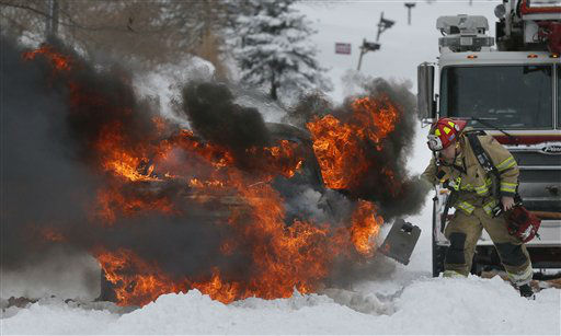 A Lawrence Firefighter places wheel blocks as he prepares to extinguish a vehicle fire in Lawrence, Kan., Thursday, Feb. 21, 2013. The car caught on fire trying to make it up a snow covered hill on Lawrence Avenue. &#40;AP Photo&#47;Orlin Wagner&#41; <span class=meta>(AP Photo&#47; Orlin Wagner)</span>