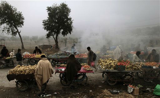 Pakistani fruit vendors, wrap themselves with shawls during a foggy and cold morning, as they wait for customers on a roadside on the outskirts of Islamabad, Pakistan, Wednesday, Jan. 2, 2013. &#40;AP Photo&#47;Muhammed Muheisen&#41; <span class=meta>(AP Photo&#47; Muhammed Muheisen)</span>