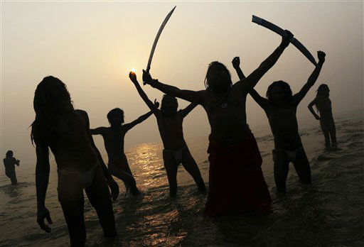 Indian Hindu holy men, or Sadhus, are silhouetted as they celebrate in the water at Sangam, the confluence of the rivers Ganges, Yamuna and mythical Saraswati, during the royal bath on Makar Sankranti at the start of the Maha Kumbh Mela in Allahabad, India, Monday, Jan. 14, 2013. Millions of Hindu pilgrims are expected to take part in the large religious congregation that lasts more than 50 days on the banks of Sangam during the Maha Kumbh Mela in January 2013, which falls every 12th year. &#40;AP Photo&#47;Kevin Frayer&#41; <span class=meta>(AP Photo&#47; Kevin Frayer)</span>
