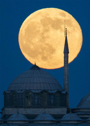 A supermoon rises behind a building of the Topkapi Palace in Istanbul, Turkey, Sunday, June 23, 2013. The moon, which will reach its full stage on Sunday, is expected to be 13.5 percent closer to earth during a phenomenon known as supermoon. The &#34;Supermoon&#34; happens only once this year as the moon on its elliptical orbit is at its closest point to earth. &#40;AP Photo&#47;Gero Breloer&#41; <span class=meta>(AP Photo&#47; Gero Breloer)</span>
