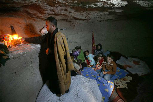 A defected Syrian policeman, Adnan al-Hamod, 33, lights a kerosene lamp at an underground cave used for shelter from Syrian governemnt forces shelling and airstrikes, at Jirjanaz village, in Idlib province, Syria, Thursday Feb. 28, 2013. Across northern Syria, rebels, soldiers, and civilians are making use of the country&#39;s wealth of ancient and medieval antiquities to protect themselves from Syria&#39;s two-year-old war. They are built of thick stone that has already withstood centuries, and are often located in strategic locations overlooking towns and roads. &#40;AP Photo&#47;Hussein Malla&#41; <span class=meta>(AP Photo&#47; Hussein Malla)</span>