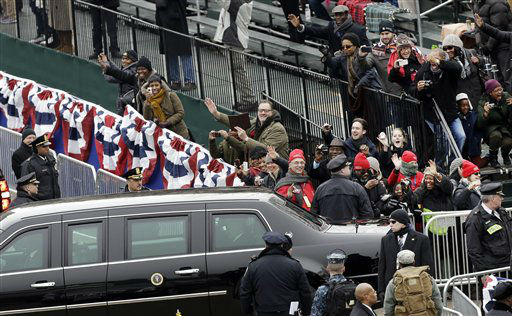 People wave at President Barack Obama and Vice President Joe Biden as their limousine passes Monday, Jan. 21, 2013, in Washington.  &#40;AP Photo&#47;Charlie Neibergall &#41; <span class=meta>(AP Photo&#47; Charlie Neibergall)</span>