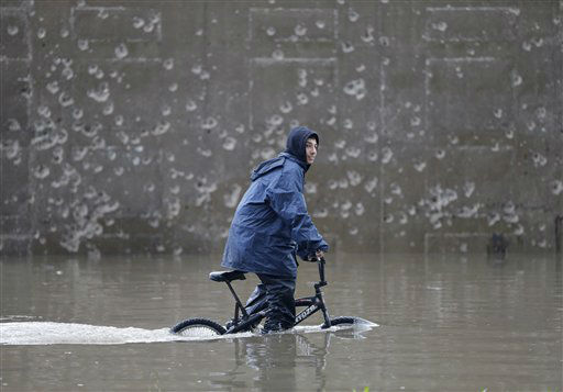 A Lebanese boy, rides his bicycle as he makes his way through a flooded highway, in Beirut, Lebanon, Monday Jan. 7, 2013. Lebanon has been hit with a snow storm that has blocked roads in the mountains and brought heavy rain showers to the capital Beirut and other coastal areas since Sunday. &#40;AP Photo&#47;Hussein Malla&#41; <span class=meta>(AP Photo&#47; Hussein Malla)</span>