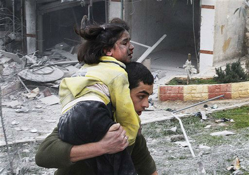 Syrian man carries his sister who was wounded in a government airstrike hit the neighborhood of Ansari, in Aleppo, Syria, Sunday, Feb. 3, 2013.  The Britain-based activist group Syrian Observatory for Human Rights, which opposes the regime, said government troops bombarded a building in Aleppo&#39;s rebel-held neighborhood of Eastern Ansari that killed over 10 people, including at least five children. &#40;AP Photo&#47;Abdullah al-Yassin&#41; <span class=meta>(AP Photo&#47; Abdullah al-Yassin)</span>