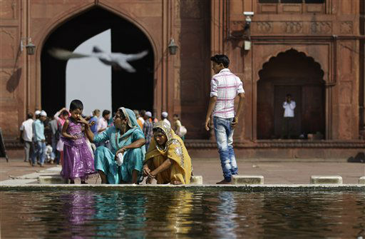 Indian Muslim women wash themselves near a fountain as a pigeon flies by at the Jama Masjid, or the Grand Mosque, in New Delhi, India, Friday, Sept. 28, 2012. The Jama Masjid is one of India&#39;s biggest mosques. &#40;AP Photo&#47;Altaf Qadri&#41; <span class=meta>(AP Photo&#47; Altaf Qadri)</span>