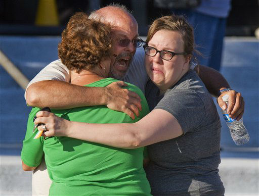Tom Sullivan, center, embraces family members outside Gateway High School where he has been searching franticly for his son Alex Sullivan who celebrated his 27th birthday by going to see &#34;The Dark Knight Rises,&#34; movie where a gunman opened fire Friday, July 20, 2012, in Aurora, Colo. &#40;AP Photo&#47;Barry Gutierrez&#41; <span class=meta>(AP Photo&#47; Barry Gutierrez)</span>