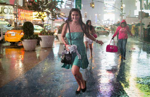 A pedestrian smiles as she runs through a torrential downpour in Times Square, Thursday, July 26, 2012, in New York. &#40;AP Photo&#47;John Minchillo&#41; <span class=meta>(AP Photo&#47; John Minchillo)</span>