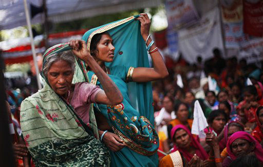 Indian village women adjust their saris, listening to a speaker, unseen, as the economically backward protesters stage a rally demanding pension for elderly poor citizens in New Delhi, India, Tuesday, March 5, 2013. &#40;AP Photo&#47;Altaf Qadri&#41; <span class=meta>(AP Photo&#47; Altaf Qadri)</span>