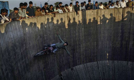 Pakistanis watch as an acrobat rides his motorcycle around a circular track, at an entertainment park set up outside a shrine in Rawalpindi, Pakistan, Wednesday, June 19, 2013. &#40;AP Photo&#47;Muhammed Muheisen&#41; <span class=meta>(AP Photo&#47; Muhammed Muheisen)</span>